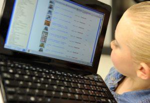 Una bambina osserva la tastiera di un computer portatile in una foto d'archivio. ANSA / FRANCO SILVI